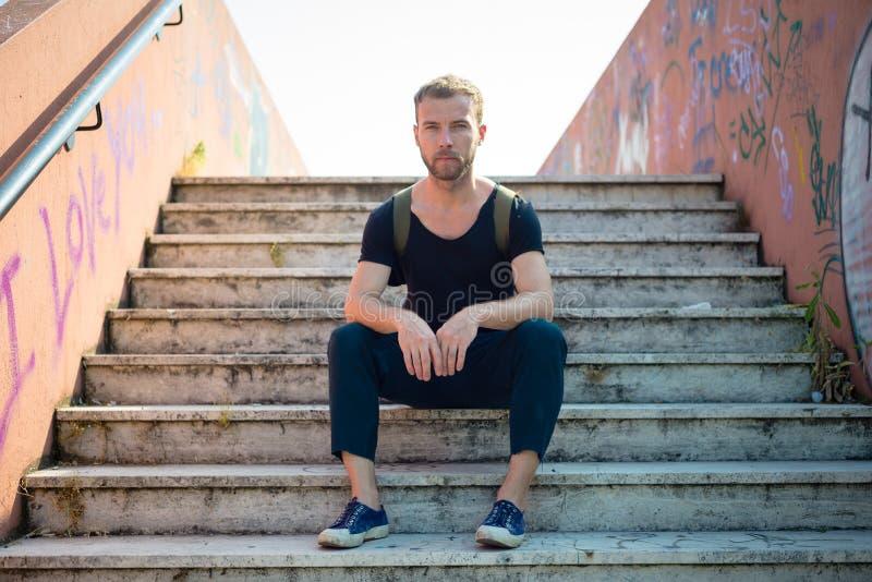 Uomo biondo alla moda moderno dei pantaloni a vita bassa che si siede in scale fotografia stock libera da diritti