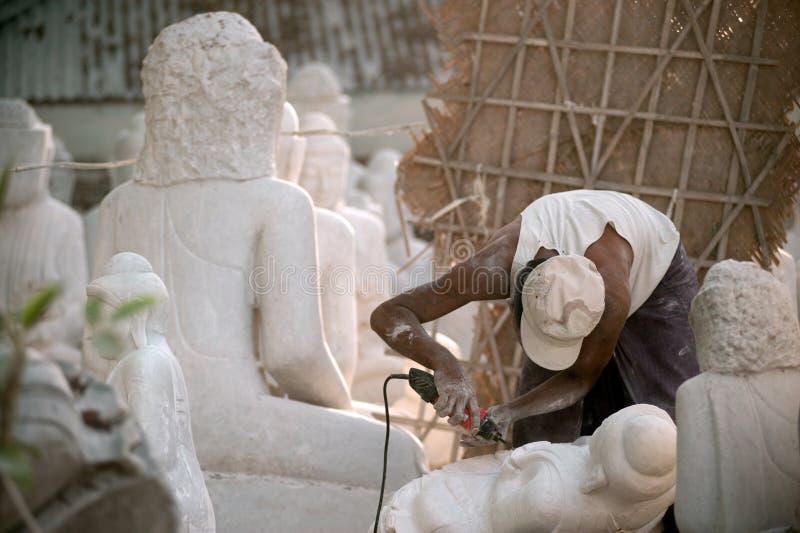 Uomo birmano che scolpisce una grande statua di marmo di Buddha fotografie stock