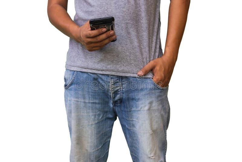 Uomo in blue jeans facendo uso dello Smart Phone e delle mani in buttero immagine stock