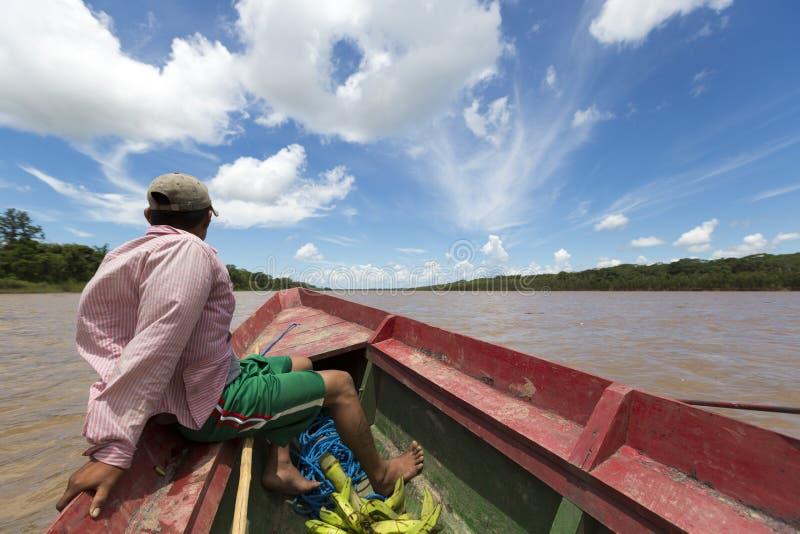 Uomo boliviano locale che viaggia su una barca di legno sul fiume di Beni, Ru immagine stock