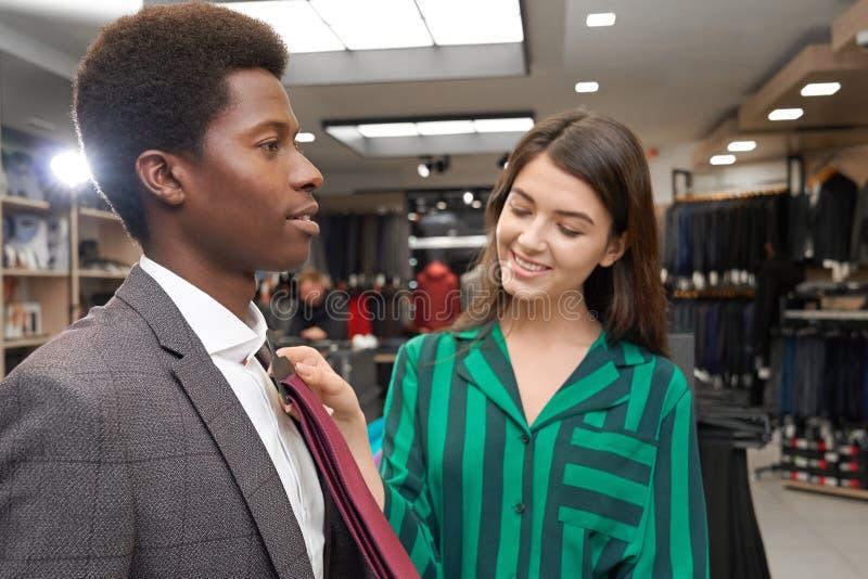 Uomo in boutique che sceglie legame, aiuto sorridente dell'assistente fotografia stock