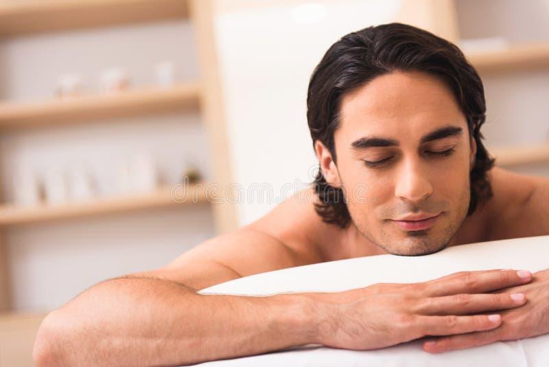 Uomo calmo che si sente bene nel salone della stazione termale immagine stock libera da diritti