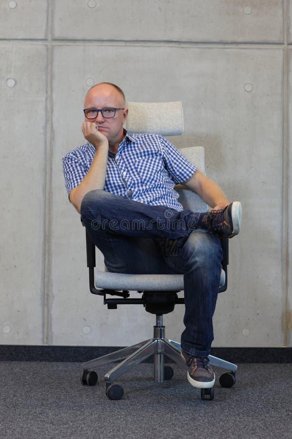 Uomo calvizia di medio evo con la cattiva posizione seduta degli occhiali sulla sedia in ufficio immagine stock