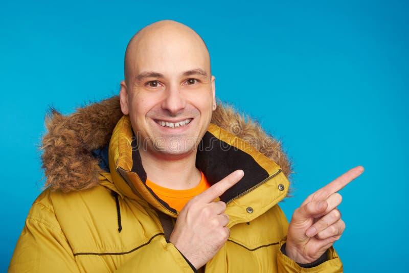 Uomo calvo in cappotto di inverno che indica le dita immagini stock libere da diritti