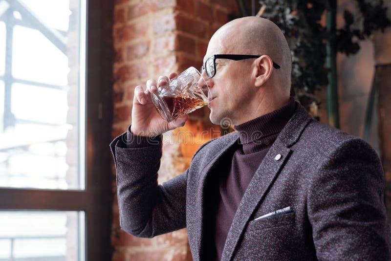 Uomo calvo che assaggia whisky immagini stock