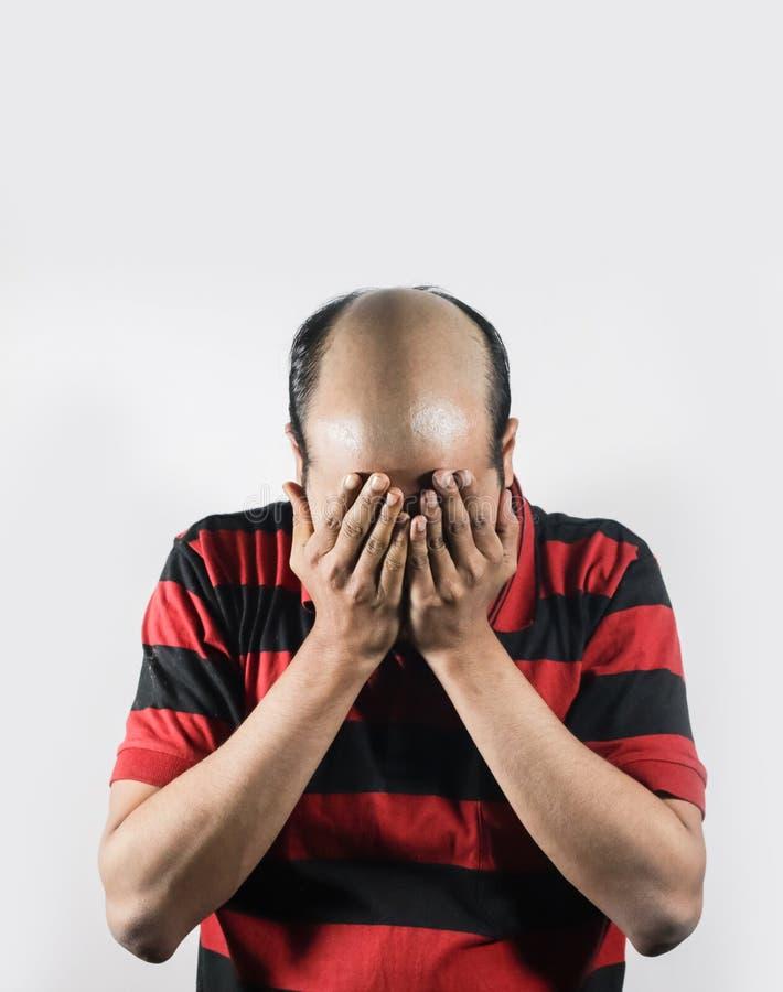 Uomo calvo che copre il suo fronte nella vergogna nel fondo bianco di spazio per testo immagine stock libera da diritti