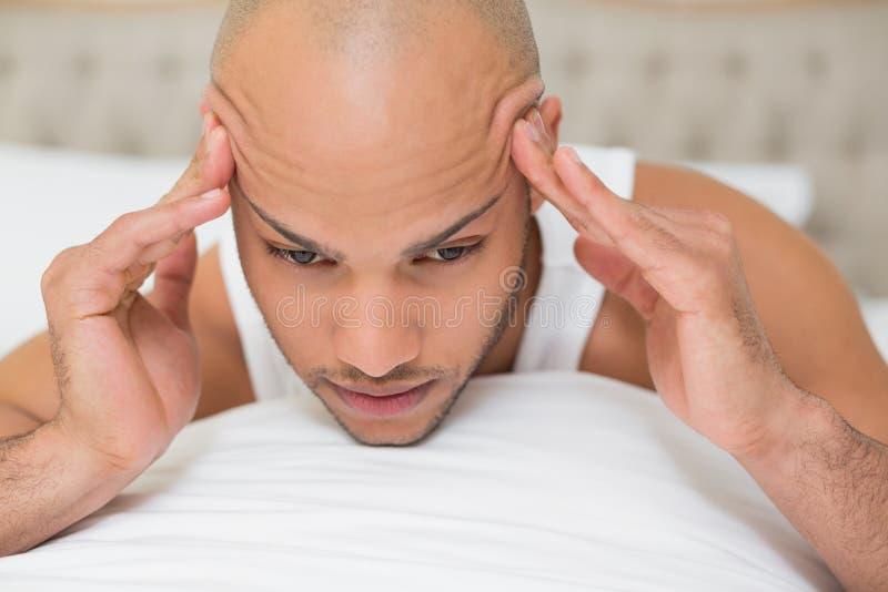 Uomo calvo che soffre dall'emicrania a letto fotografie stock