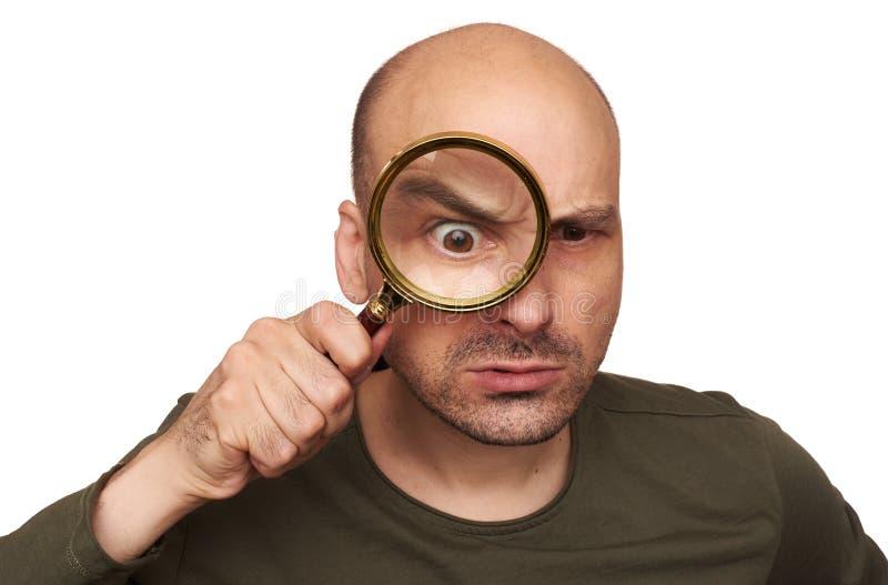 Uomo calvo colpito che guarda tramite la lente d'ingrandimento fotografia stock libera da diritti