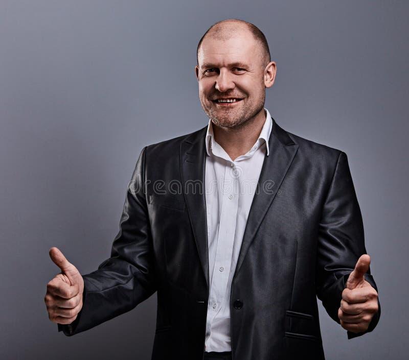 Uomo calvo comico di affari di divertimento in vestito nero che mostra il pollice di successo del dito sul segno su fondo grigio  fotografia stock