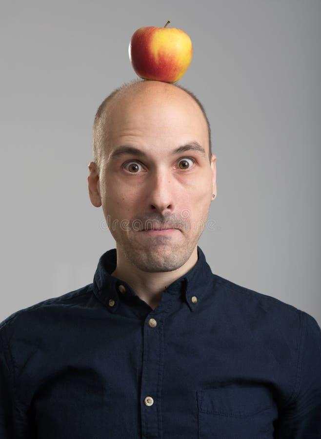 Uomo calvo con una mela sulla sua testa fotografie stock libere da diritti
