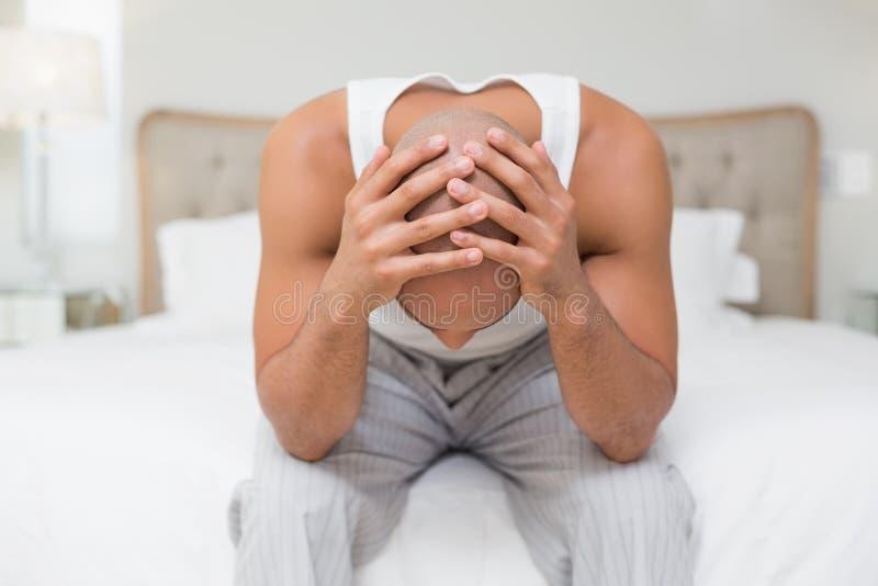 Uomo calvo premuroso con la testa in mani sul letto fotografie stock