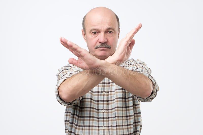 Uomo calvo senior con i baffi che fanno il fanale di arresto con la mano Vi non dò un permesso immagini stock