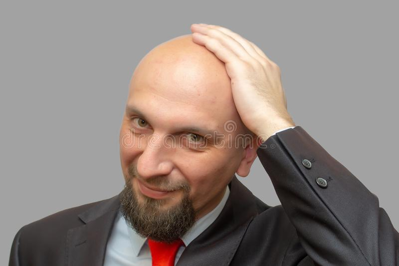 Uomo calvo in vestito, testa rasa, fondo grigio fotografie stock