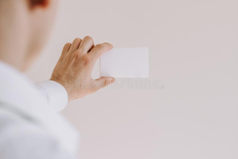 Uomo in camicia bianca che mostra una carta in bianco immagini stock libere da diritti