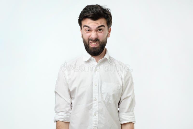 Uomo in camicia bianca isolata contro il fondo bianco dello studio Il suo fronte è nello smorfia di repulsione immagini stock