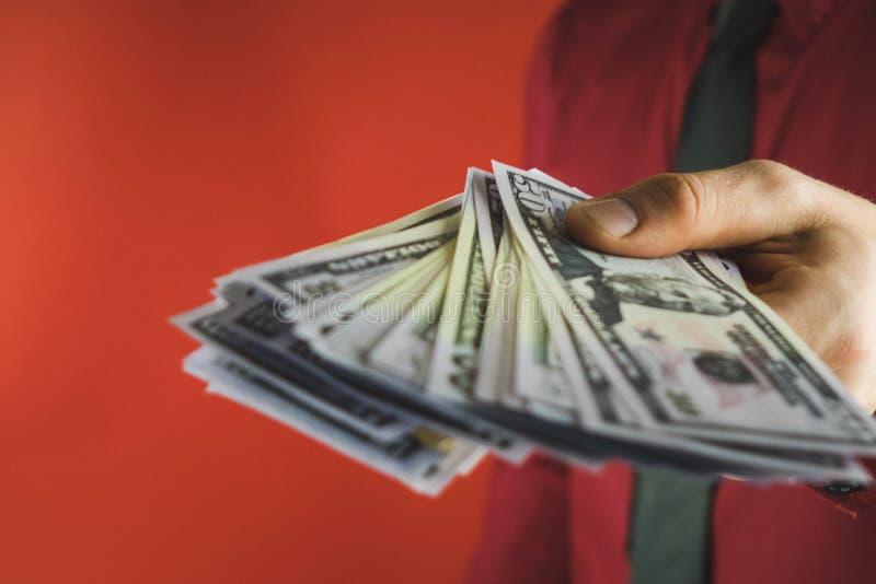 uomo in camicia rossa con una tenuta un pacchetto delle fatture in sua mano su un fondo rosso fotografie stock