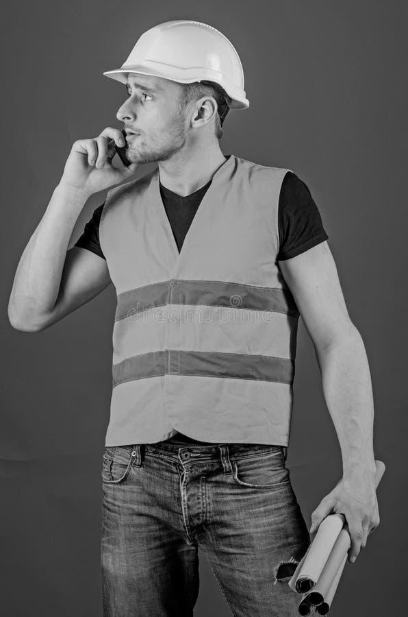 Uomo, caporeparto in casco che parla sul telefono, fondo rosso Architetto che chiama ingegnere per riparare piano Ingegnere, arch immagini stock libere da diritti