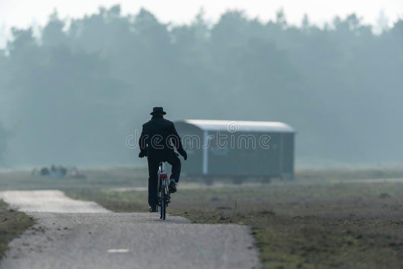 Uomo in cappello che cicla sul percorso nella riserva naturale nebbiosa fotografia stock libera da diritti