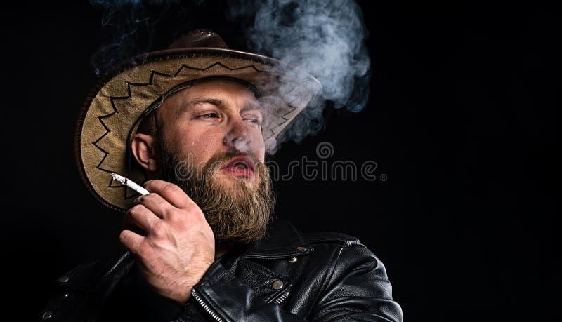 Uomo in cappello da cowboy con una sigaretta in sua mano immagine stock libera da diritti