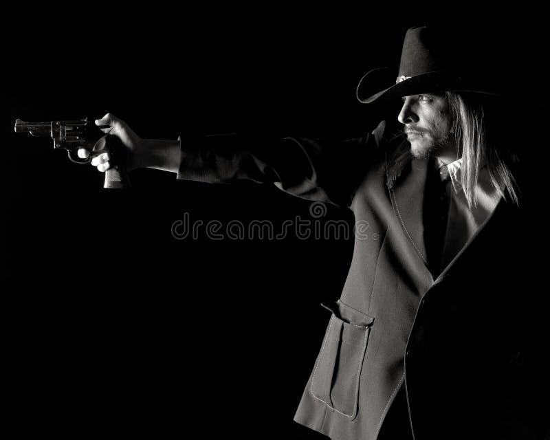 Uomo in cappello del cowboy che mira pistola. fotografia stock