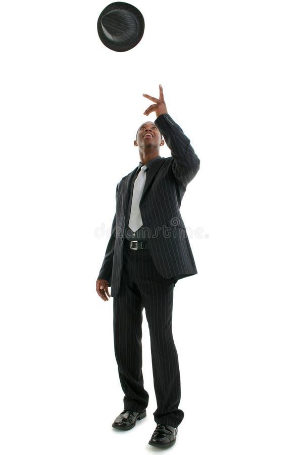Uomo in cappello di lancio del vestito Pinstriped in aria fotografia stock