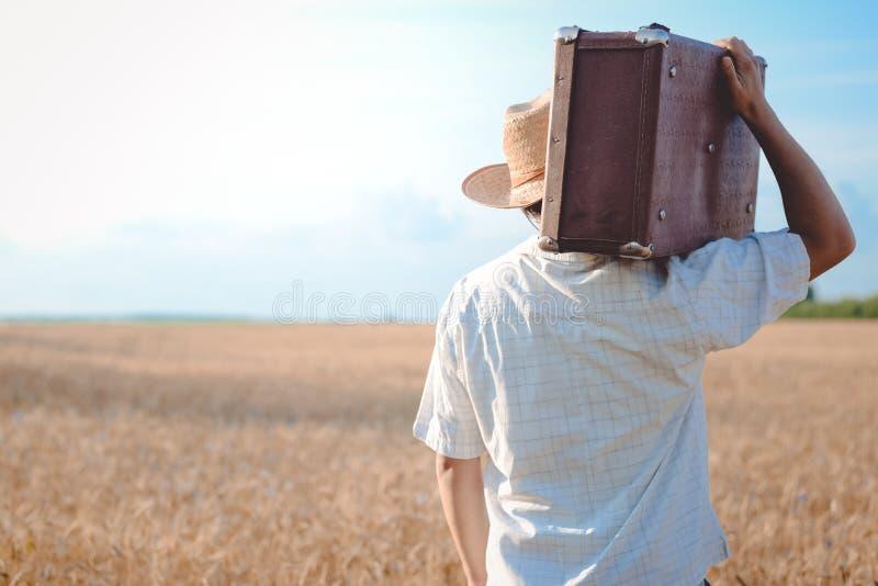 Uomo in cappello di paglia con una retro valigia sul suo fotografie stock libere da diritti