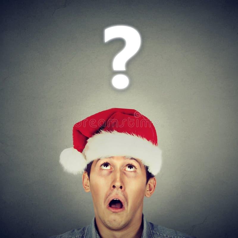 Uomo in cappello di Santa che interroga circa i regali immagine stock libera da diritti