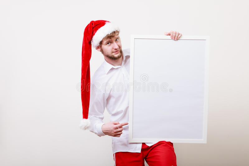 Uomo in cappello di Santa con l'insegna in bianco Copi lo spazio immagine stock