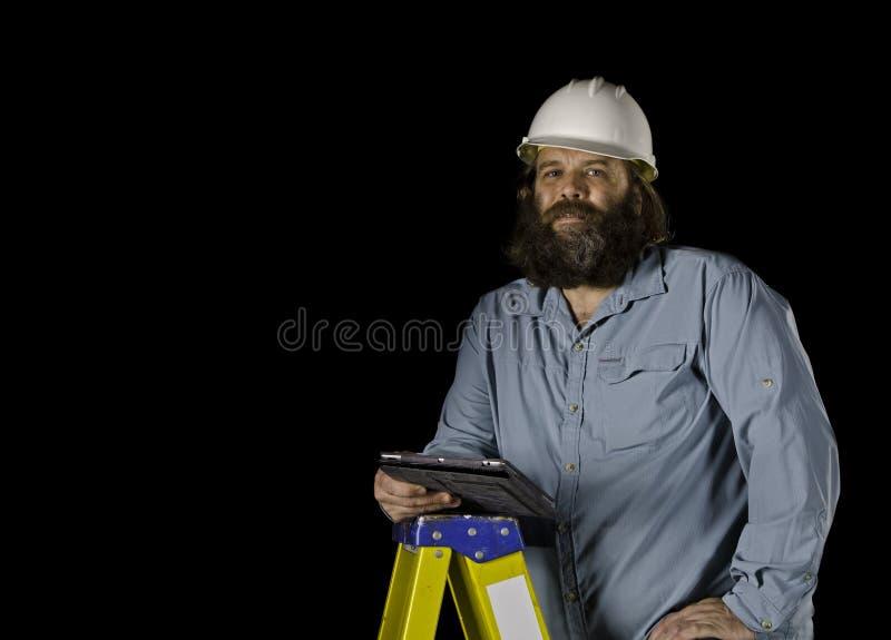 Uomo in cappello duro che tiene un ridurre in pani su una scaletta di punto fotografia stock libera da diritti