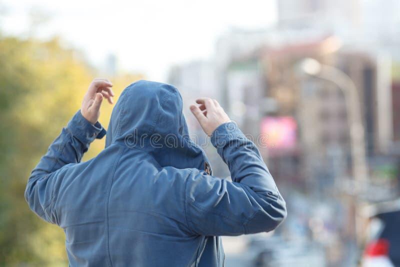 Uomo in cappuccio, distogliente lo sguardo, paesaggio urbano dietro lui immagini stock libere da diritti