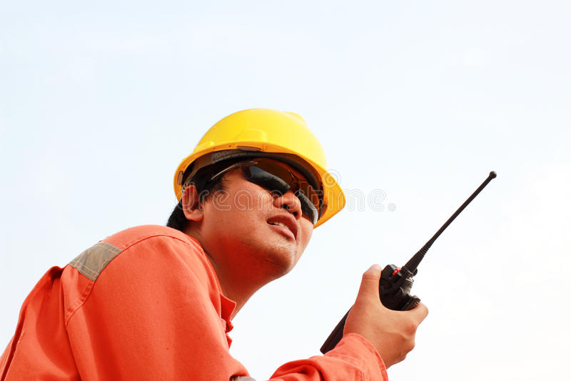 Uomo in casco facendo uso del walkie-talkie fotografia stock