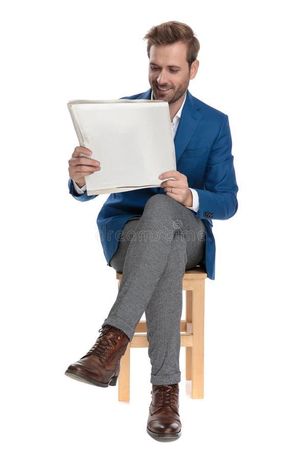 Uomo casuale allegro che legge un giornale e sorridere immagini stock libere da diritti