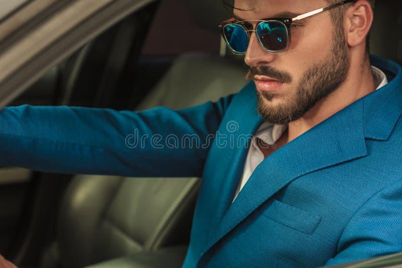 Uomo casuale astuto attraente con gli occhiali da sole che conducono la sua automobile immagine stock libera da diritti