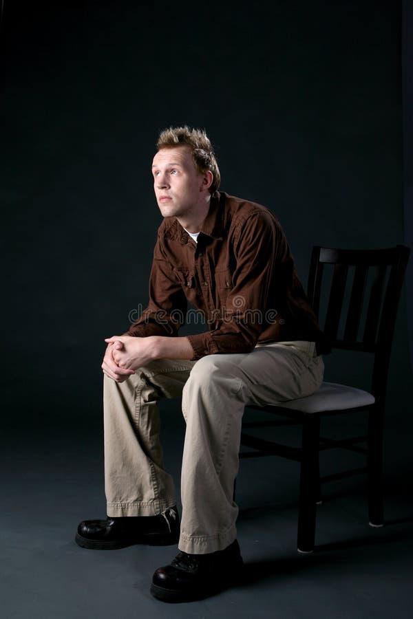 Uomo casuale che si siede in una presidenza e che osserva in su fotografie stock