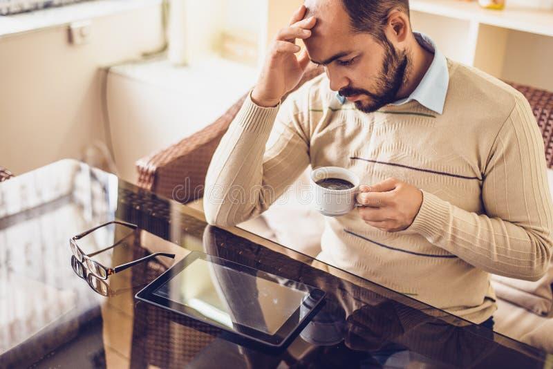 Uomo casuale che utilizza il computer della compressa che si siede in Internet praticante il surfing del caffè fotografie stock