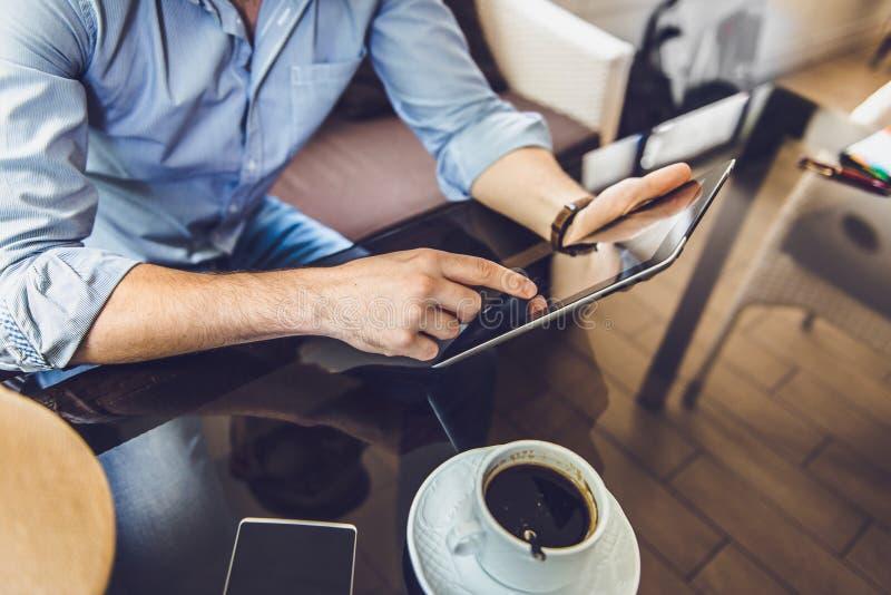 Uomo casuale che utilizza il computer della compressa che si siede nell'interno praticante il surfing del caffè immagini stock libere da diritti