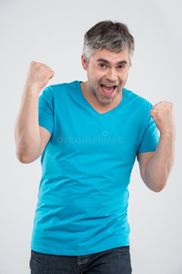 Uomo casuale che vince e che celebra sopra il fondo bianco fotografie stock libere da diritti