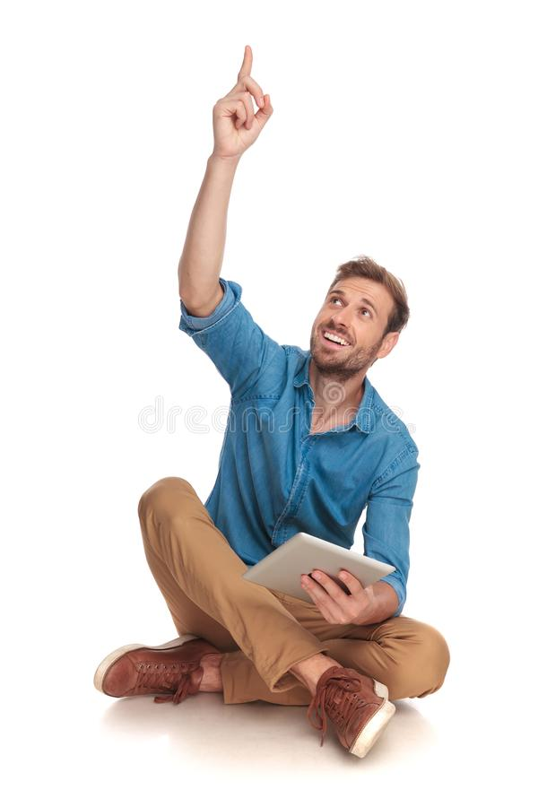 Uomo casuale felice che celebra successo mentre lavorando alla compressa immagini stock