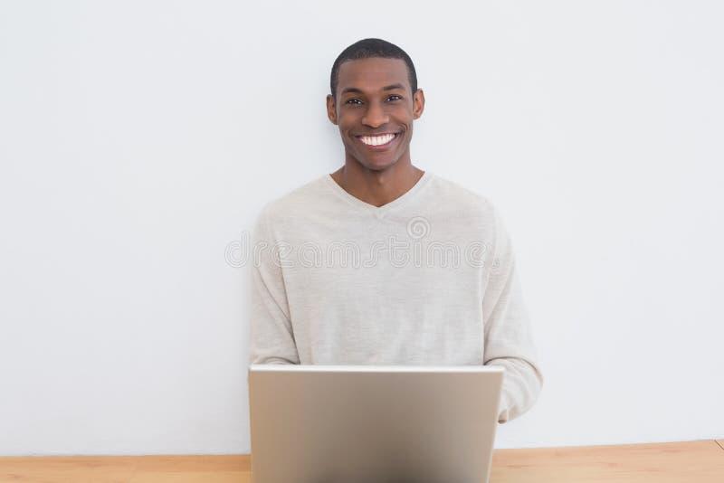 Uomo casuale felice di afro che per mezzo del computer portatile sul pavimento immagine stock