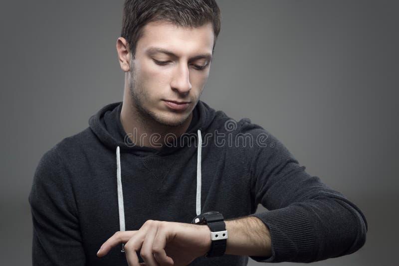Uomo casuale moderno sportivo in maglia con cappuccio che controlla tempo sul suo orologio immagini stock libere da diritti