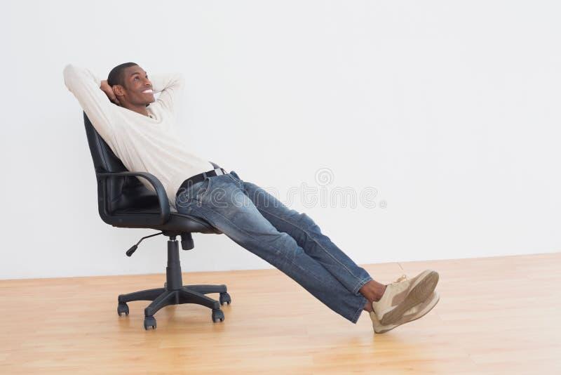 Uomo casuale premuroso che si siede sulla sedia dell'ufficio nella stanza vuota fotografie stock