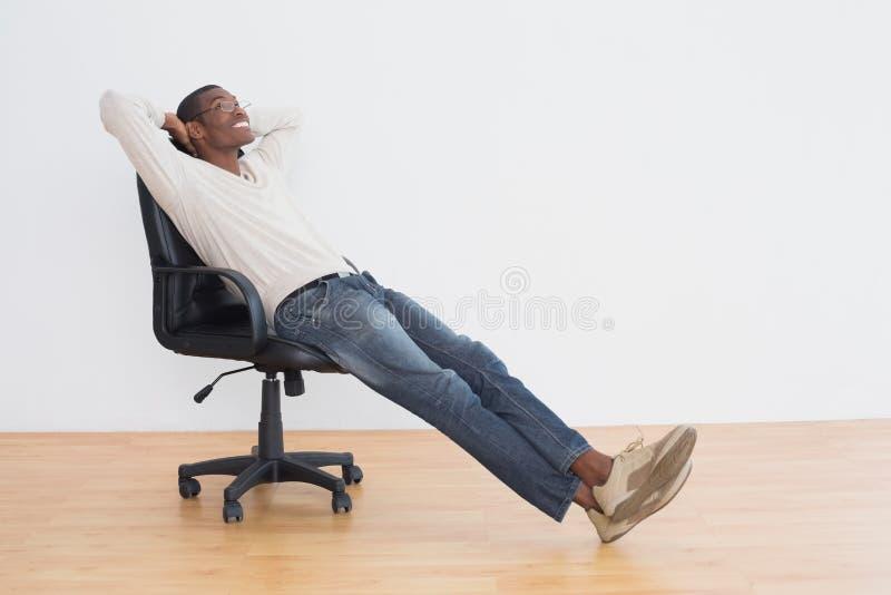 Uomo casuale premuroso di afro che si siede sulla sedia dell'ufficio nella stanza vuota fotografie stock