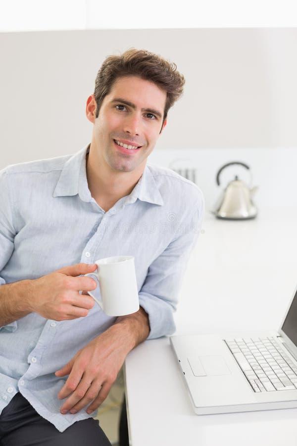Uomo casuale sorridente con la tazza di caffè con il computer portatile a casa immagine stock