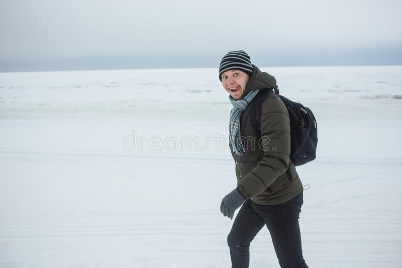Uomo caucasico alla moda che fa un'escursione sulla neve coperta della costa di mare Lui espressione divertente del fronte di rap fotografia stock
