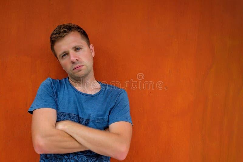 Uomo caucasico brutale che sta vicino alla parete rossa immagine stock
