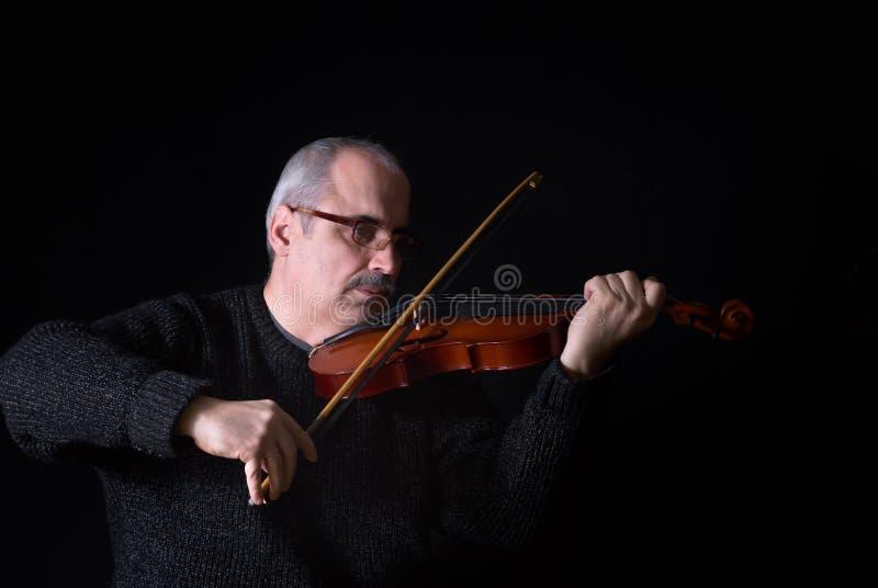 Uomo caucasico che gioca il violino nell'oscurità immagini stock libere da diritti