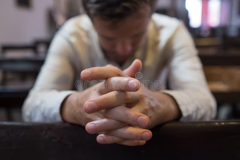 Uomo caucasico che prega nella chiesa Ha problemi e chiede Dio aiuto fotografia stock libera da diritti
