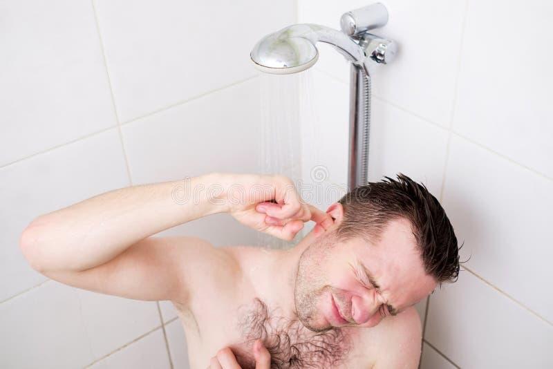 Uomo caucasico che pulisce il suo orecchio mentre prendendo una doccia e una condizione sotto l'acqua corrente fotografie stock libere da diritti