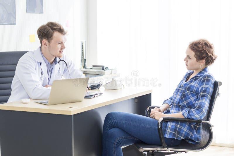 Uomo caucasico dei professionisti medici che rassicura e che parla con il paziente di sforzo della giovane donna immagini stock