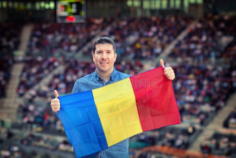 Uomo caucasico felice che tiene bandiera nazionale rumena in mani sostenitore al †internazionale di avvenimento sportivo «ad in fotografia stock libera da diritti